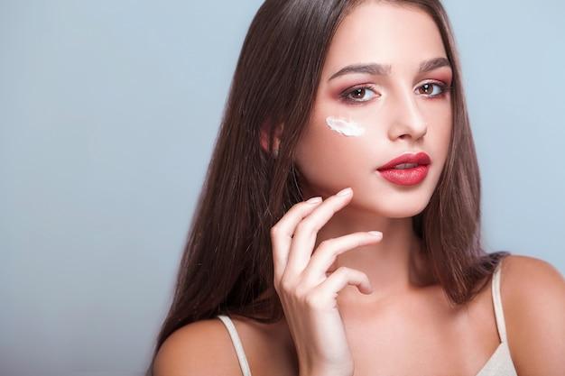 Trattamento viso. donna con il viso sano, applicare la crema cosmetica sotto gli occhi