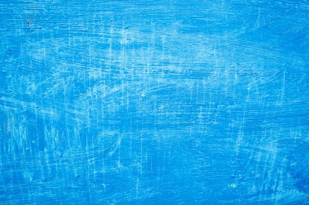 Tratti strutturati di vernice blu sulla superficie in legno.