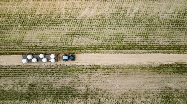Trattore cavalca sul campo e trasporta balle di fieno vista aerea