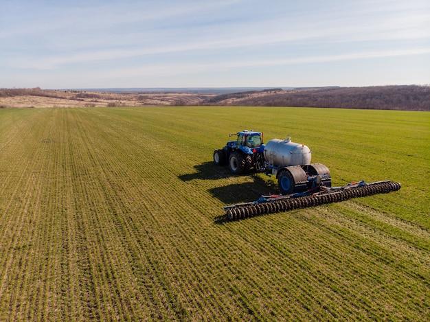 Trattore che applica fertilizzanti minerali liquidi al suolo sul frumento autunnale