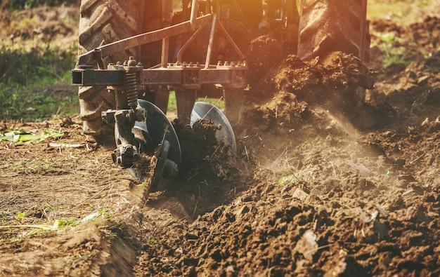 Trattore che ara i campi che preparano terra per seminare