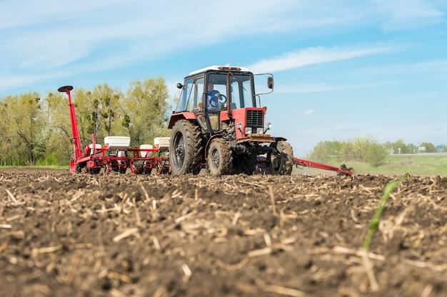Trattore con la piantatrice nel campo con cielo blu