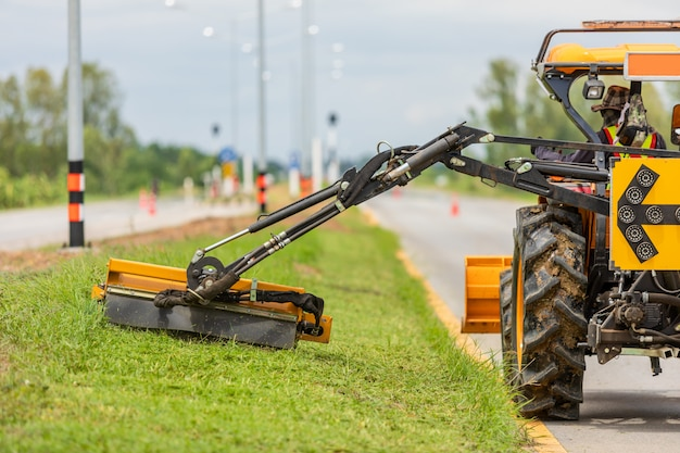 Trattore con una falciatrice meccanica che falcia erba sul lato della strada asfaltata