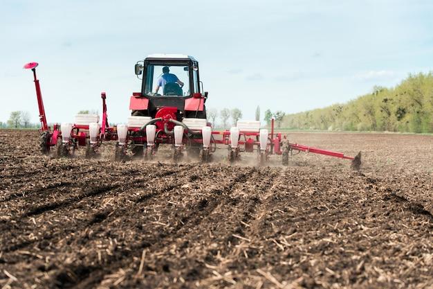 Trattore delle seminatrici in un campo di terra nera con trapani agricoli di un seme trainato