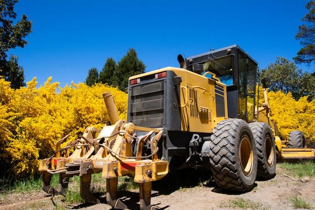 Trattore giallo su terreno agricolo.