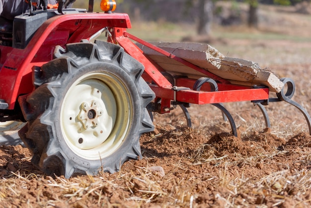 Trattore rosso con l'aratro che ara vista alta vicina del suolo del campo.