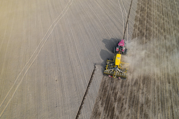 Trattore su un campo arato, vista dall'alto. campo agricolo per piantare ortaggi. il trattore fa solchi sul campo.