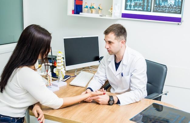 Traumatologo che esamina le mani pazienti in ospedale moderno