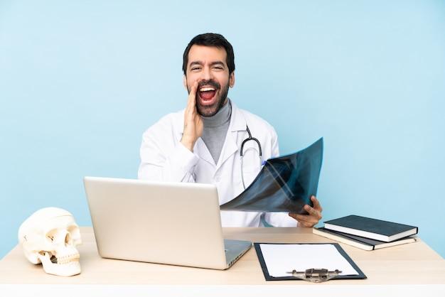 Traumatologo professionista nel posto di lavoro che grida con la bocca spalancata