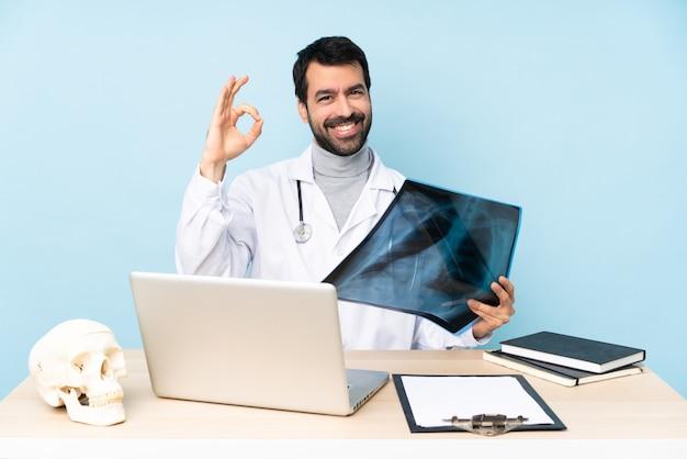 Traumatologo professionista nel posto di lavoro che mostra segno giusto con le dita