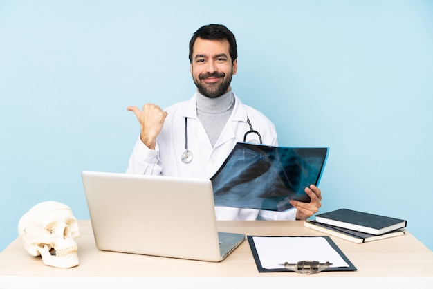 Traumatologo professionista sul posto di lavoro che punta verso il lato per presentare un prodotto