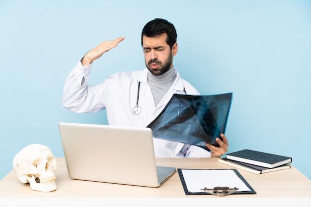Traumatologo professionista sul posto di lavoro con espressione stanca e malata