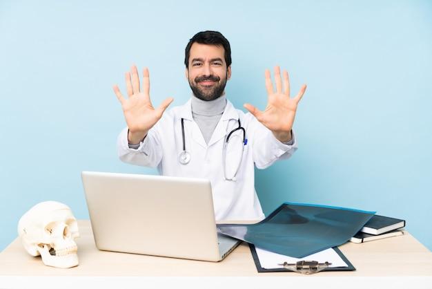 Traumatologo professionista sul posto di lavoro contando dieci con le dita