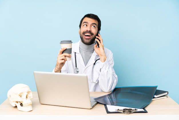 Traumatologo professionista sul posto di lavoro in possesso di caffè da portare via e un cellulare