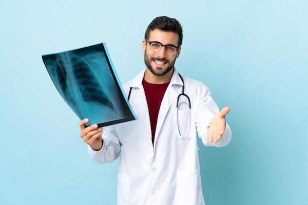 Traumatologo professionista tenendo la radiografia isolata su handshaking blu dopo un buon affare