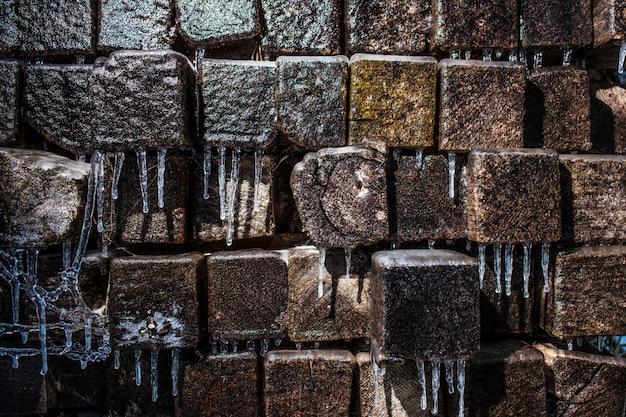 Travi e ghiaccioli di legno coperti di ghiaccio