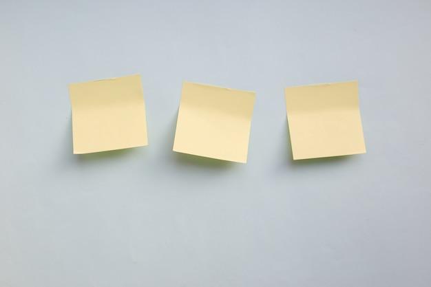 Tre adesivi di carta gialla nota con copia spazio su sfondo blu