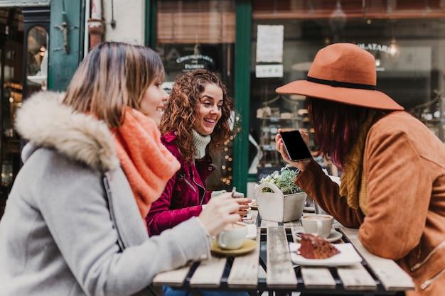 Tre amiche che mangiano caffè in una terrazza a oporto, portogallo. avere una conversazione divertente