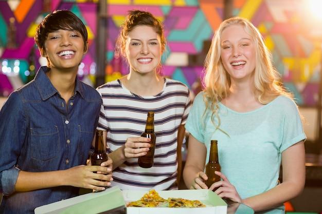 Tre amiche che mangiano una bottiglia di birra e pizza in festa