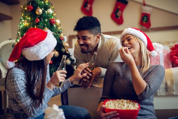 Tre amici alla moda attraenti che bevono birra e mangiano popcorn mentre parlano di cose divertenti