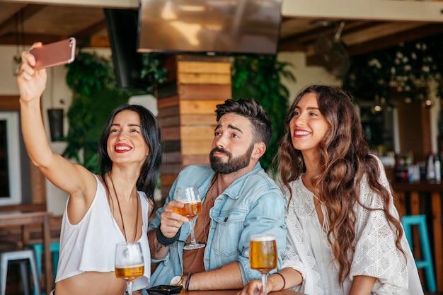 Tre amici che prendono selfie nel bar