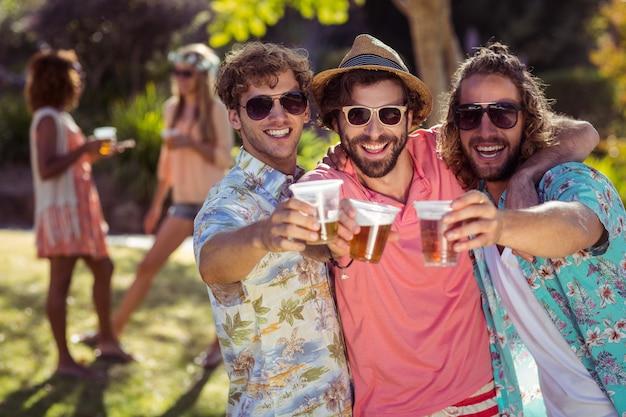 Tre amici che tostano bicchieri di birra
