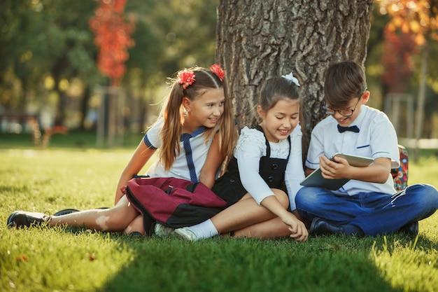 Tre amici di scuola adolescenti sorridenti che si siedono nel parco sull'erba e che giocano insieme il nuovo gioco della compressa. emozioni diverse sui loro volti