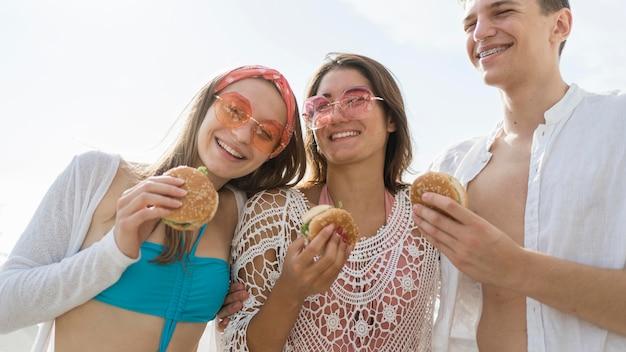 Tre amici di smiley all'aperto che mangiano hamburger insieme