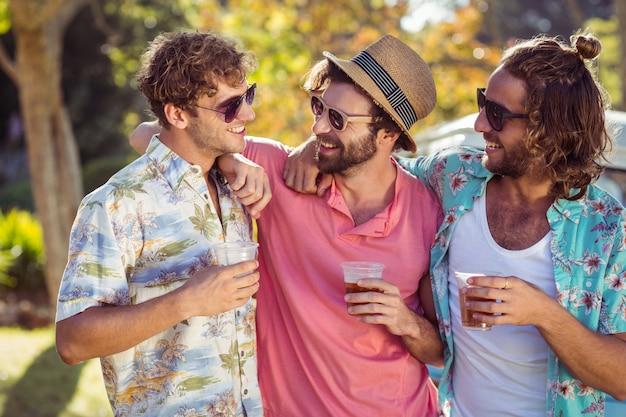 Tre amici felici in piedi con bicchieri di birra