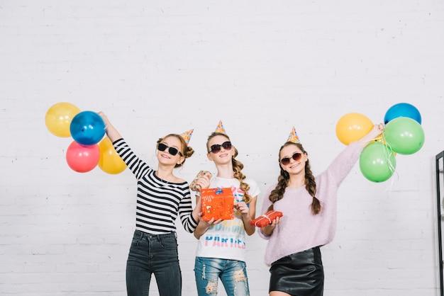 Tre amici femminili adolescenti che tengono i contenitori di regalo avvolti che stanno contro il muro