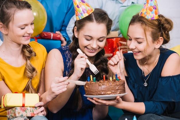 Tre amici femminili che mangiano la torta con la forchetta