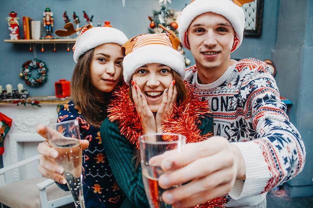 Tre amici in costumi natalizi si divertono.