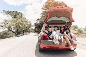 Tre amici seduti insieme nel bagagliaio di auto prendendo autoritratto sulla strada