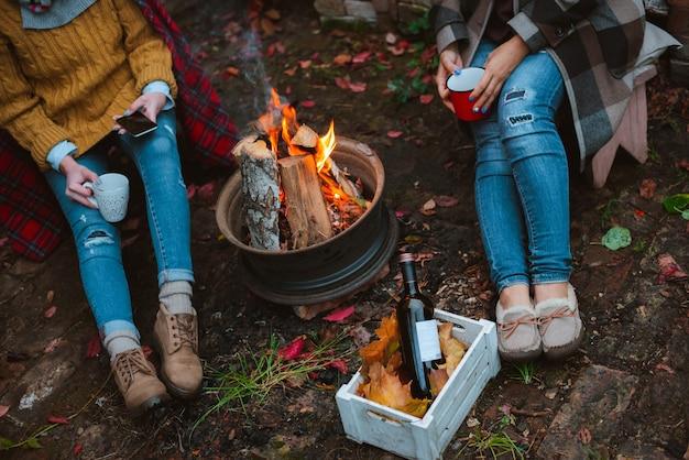 Tre amici si rilassano comodamente e bevono vino sera d'autunno all'aperto davanti al fuoco nel cortile.