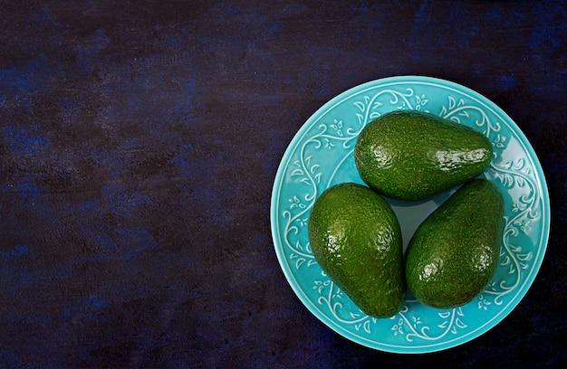 Tre avocado maturi su un tavolo scuro. concetto di cibo sano. vista dall'alto