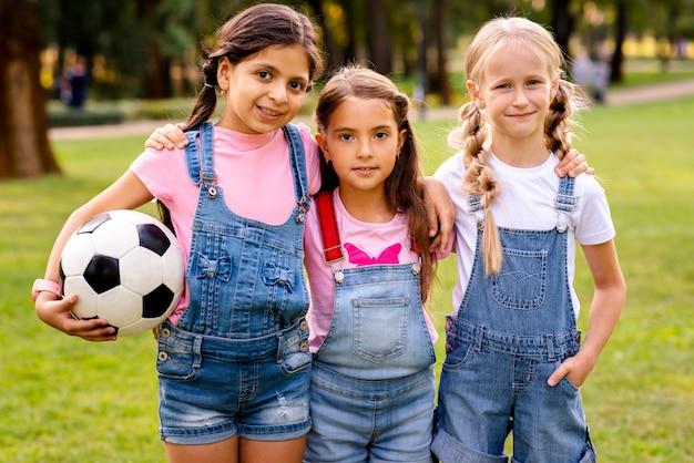 Tre bambine che posano per la macchina fotografica nel parco