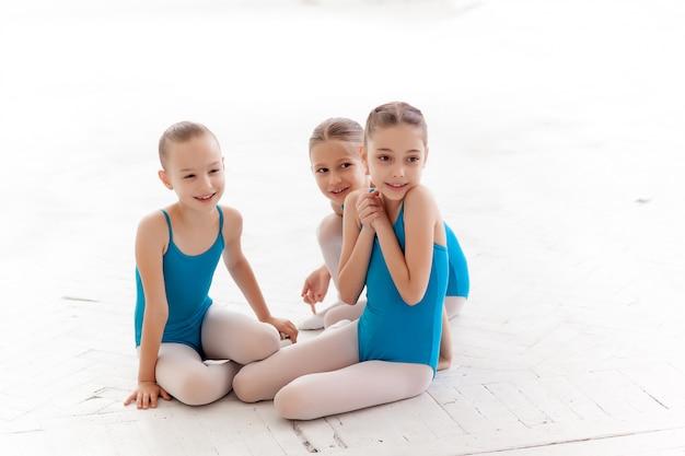 Tre bambine di balletto che si siedono e parlano insieme