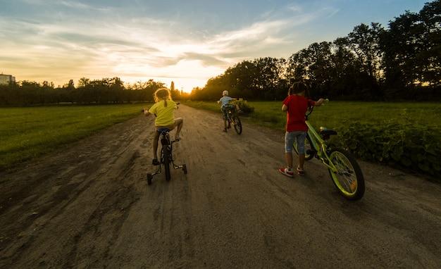 Tre bambini che vanno in bicicletta. i bambini un casco in sella a una bicicletta nel parco. bellissimi bambini