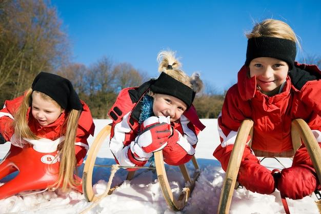 Tre bambini con toboggan nella neve