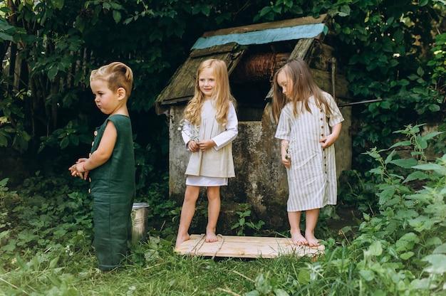 Tre bambini giocano vicino al pozzo su uno sfondo di erba e alberi