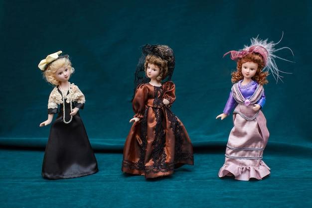 Tre bambole in classici abiti vintage e cappelli su sfondo scuro