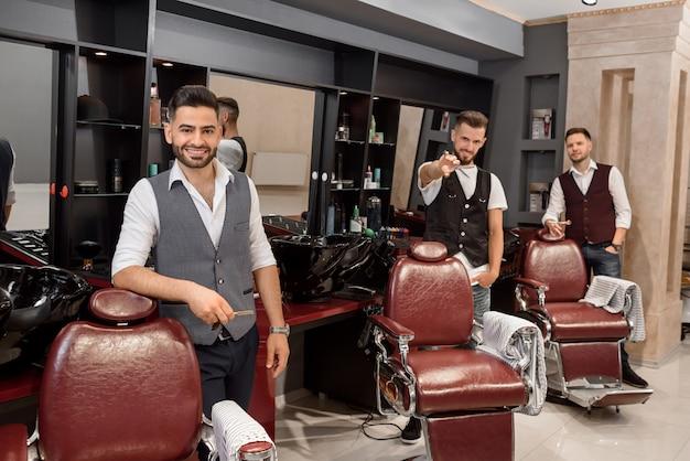 Tre barbieri belli in posa nel negozio di barbiere vicino a sedie da parrucchiere.