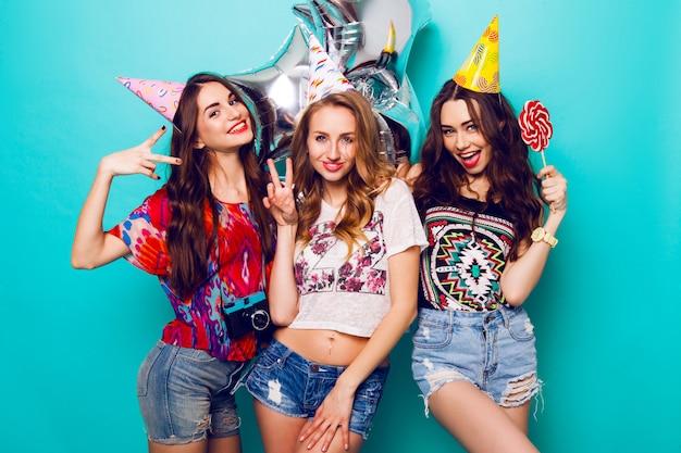 Tre belle donne felici in elegante abito estivo, cappelli di carta e palloncini di purezza divertirsi e festeggiare il compleanno. sfondo blu colorato. la ragazza graziosa tiene un grande lecca-lecca.