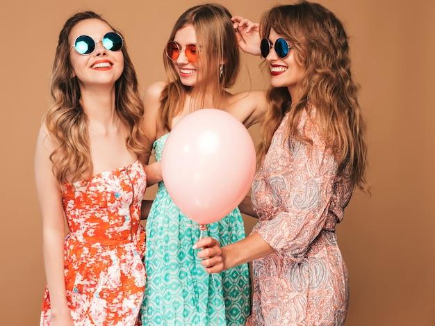 Tre belle donne sorridenti in abiti a scacchi estate camicia. ragazze in posa modelli con palloncini colorati in occhiali da sole. divertirsi, pronti per la festa di compleanno o festa