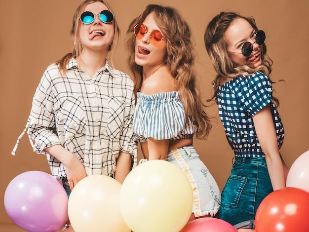 Tre belle donne sorridenti in abiti a scacchi estate camicia. ragazze in posa modelli con palloncini colorati in occhiali da sole. divertirsi, pronti per la festa di compleanno