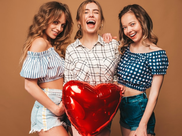 Tre belle donne sorridenti in abiti a scacchi estate camicia. ragazze in posa modelli con palloncino a forma di cuore rosso in occhiali da sole. pronto per la festa di san valentino