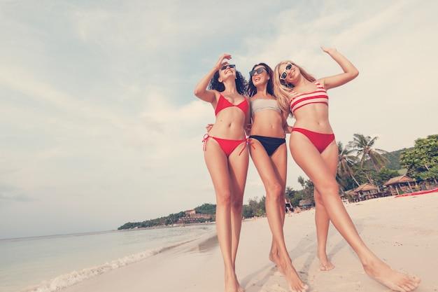 Tre belle giovani amiche snelle europee in bikini a strisce rosse e luminose camminano su una spiaggia tropicale in vacanza, felicità gioia estate e divertimento