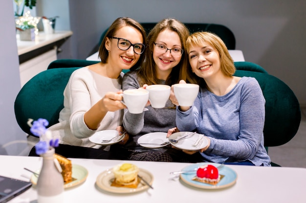 Tre belle ragazze caucasiche trascorrono del tempo insieme bevendo caffè nel caffè, divertendosi e mangiando torte e dessert.