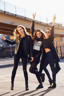 Tre belle ragazze che si divertono all'aperto. umore urbano di stile di vita. sfondo della città di sera. migliori amiche che indossano abiti casual neri.