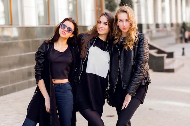 Tre belle ragazze che si divertono insieme all'aperto. umore urbano di stile di vita. sfondo centro città. migliori amiche che indossano abiti casual neri.